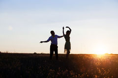 Young couple silhouettes dancing on the field. At sunset Royalty Free Stock Image