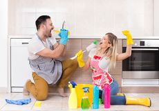 Man and woman singing after finishing chores. Young couple singing and having fun on kitchen floor after finishing chores royalty free stock photo