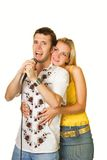 Young couple singing karaoke. Attractive young couple singing karaoke isolated on white background Royalty Free Stock Photos