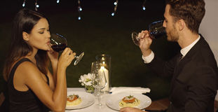 Young couple sipping red wine during dinner Royalty Free Stock Image