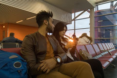 Young Couple Sit In Airport Lounge Waiting Departure Hispanic Man And Woman Use Cell Smart Phone Stock Photo