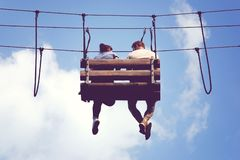 Romantic meeting in the skies, couple sitting dangling feet on a hanging bench stock images