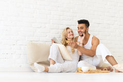 Young Couple Sit Floor, Hispanic Man Woman Using Tablet Computer Credit Card Online Payment Lovers Bedroom. Over White Brick Wall Royalty Free Stock Photo