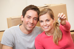 Young couple sit on the floor holding key in hand Royalty Free Stock Photos