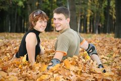 Young  couple sit in leaves Royalty Free Stock Image