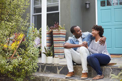 Young couple sit looking at each other outside their house Stock Images