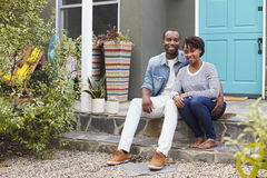 Young couple sit looking to camera outside their new house Royalty Free Stock Image