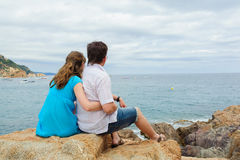 Young couple sit near the sea Stock Photos