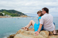 Young couple sit near the sea Stock Photo