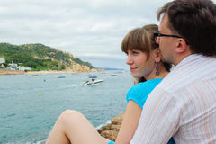 Young couple sit near the sea Royalty Free Stock Photos
