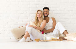Young Couple Sit On Pillows Floor, Happy Hispanic Man And Woman Breakfast Tray Lovers In Bedroom. Over White Brick Wall Royalty Free Stock Photos