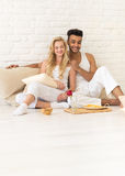 Young Couple Sit On Pillows Floor, Happy Hispanic Man And Woman Breakfast Tray Lovers In Bedroom Royalty Free Stock Images