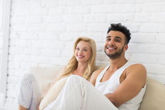 Young Couple Sit On Pillows Floor, Happy Smile Hispanic Man And Woman Lovers In Bedroom Royalty Free Stock Photos