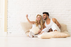 Young Couple Sit On Pillows, Girl Take Selfie Photo, Happy Smile Hispanic Man And Woman Hug Lovers. Young Couple Sit On Pillows, Girl Take Selfie Photo Hold Cell Stock Images