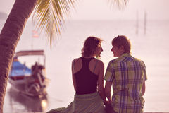 Young couple sit together under a palm tree and looking toward s Stock Photography