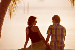 Young couple sit together under a palm tree and looking toward s Royalty Free Stock Photography