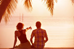 Young couple sit together under a palm tree and looking toward s Royalty Free Stock Image