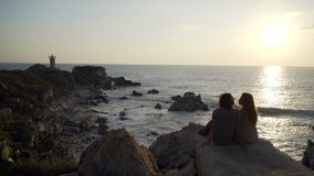 Young couple siting on the cliff. With beatiful view on the seaside at sunset stock video footage