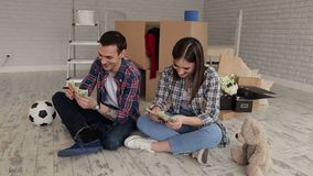 Couple is sitting in apartment and counting money. A young couple sits on the floor in their new apartment among boxes and count the money stock video