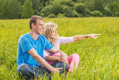 Young couple sits on grass Stock Images