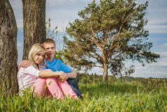Young couple sits on grass Stock Image