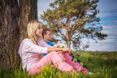 Young couple sits on grass Stock Photo