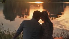 A young couple sits on a lake at sunset. A young couple sits on a lake at sunset stock footage