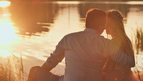 A young couple sits on a lake at sunset. A young couple sits on a lake at sunset stock video