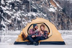 Young couple sits and laughs in tent during winter hike. Young couple sits and laughs in yellow tourist tent during winter hike on rocks background Royalty Free Stock Image