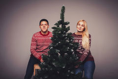 Young couple sits near a Christmas tree Royalty Free Stock Photography