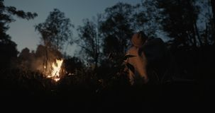 A young couple sits at night in the forest, embracing under a common plaid in front of a bonfire, talking and laughing. Young Couple Resting Camping stock footage