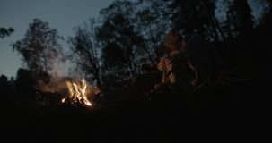 A young couple sits at night in the forest, embracing under a common plaid in front of a bonfire, talking and laughing. Young Couple Resting Camping stock video