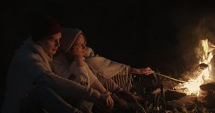 A young couple sits at night in the forest, embracing under a common plaid in front of a bonfire, talking and laughing. Young Couple Resting Camping stock video footage