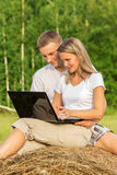 The young couple sits outdoors with the laptop Royalty Free Stock Photo