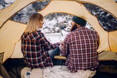 Young couple sits and smiles in tent during winter hike. Back view. Young couple sits and smiles in yellow tourist tent during winter hike. Back view Stock Images