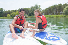 Young couple sits on standup paddle board on lake Royalty Free Stock Photos