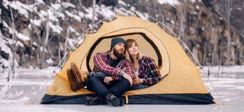 Young couple sits in tent during winter hike. Young couple sits in yellow tourist tent during winter hike on rocks background Royalty Free Stock Photography