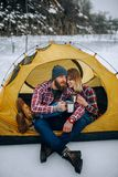 Young couple sits in tent and drinks hot tea during winter hike. Young couple sits in yellow tourist tent and drinks hot tea from mugs during winter hike Stock Images