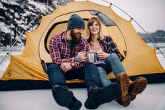 Young couple sits in tent, smiles and drinks hot tea during winter hike. Young couple sits in yellow tourist tent, smiles and drinks hot tea from mugs during Stock Photos