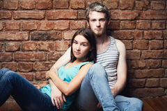 Young couple sitting against a brick wall Royalty Free Stock Images