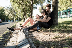 Young Couple sitting against a tree in a urban environment Royalty Free Stock Photography