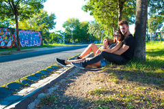 Young Couple sitting against a tree in a urban environment Royalty Free Stock Image