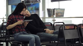 Young couple is sitting in airport waiting area. Beautiful woman is working with tablet pc playing or surfing internet, man is sleeping on her shoulder tired stock footage
