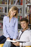 Young couple sitting in armchair with book Royalty Free Stock Photo