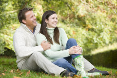 Young couple sitting in autumn woods. Young couple sitting on grass in autumn woods royalty free stock photos