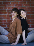 Young couple sitting back to back. A happy young couple sitting back to back in front of brick wall royalty free stock images