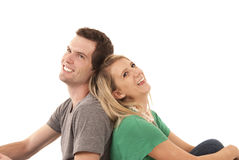 Young couple sitting back to back gazing up Royalty Free Stock Image