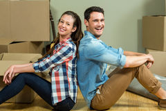 Young couple sitting back to back in their house. Young couple sitting back to back and smiling in their new house Royalty Free Stock Photography