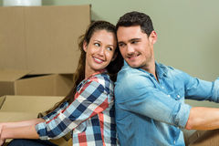 Young couple sitting back to back in their new house. Young couple sitting back to back and looking at each other in their new house Stock Photo