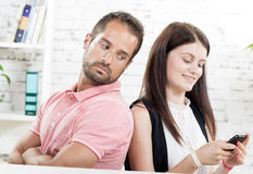 Young couple sitting back to back,. Women phone Royalty Free Stock Photo